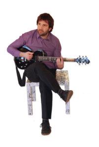 Daniel Brion assis joue de la guitare électrique.