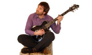 Daniel Brion est assis en tailleur et joue de la guitare électrique.